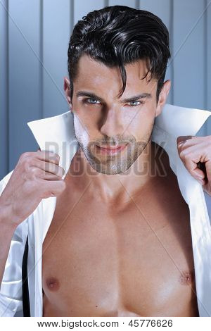 Fashion young man opening his shirt with sexy muscular chest