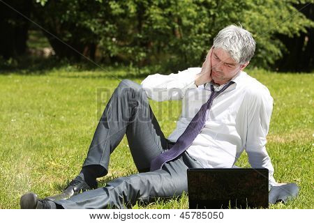 Worried businessman using laptop on a meadow