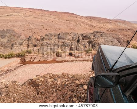 a dirty car on the edge of a ravine in the sahara desert poster