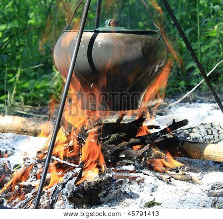 Camping kettle over burning campfire