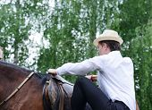Young stylish man taking riding a horse on countryside poster