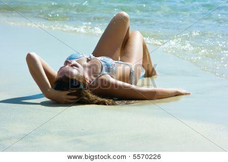 Brunette Girl Relaxing On The Beach