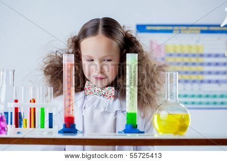 Slyly smiling girl posing with colorful test-tubes