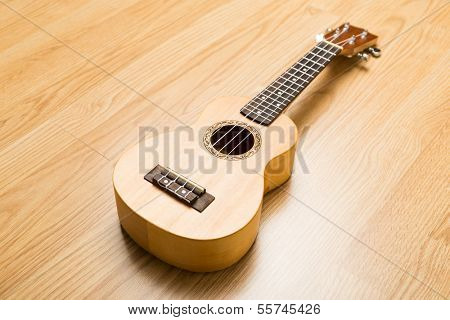 Ukulele over the wooden background