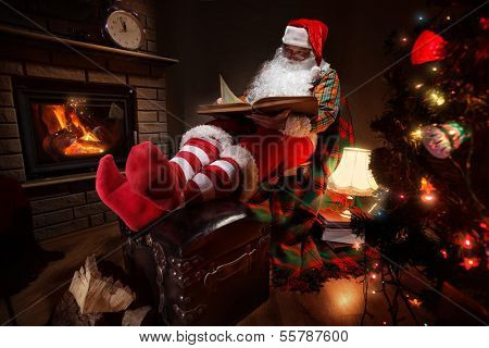 Santa Claus sitting at his room at home near Christmas tree and  resting by his fireplace