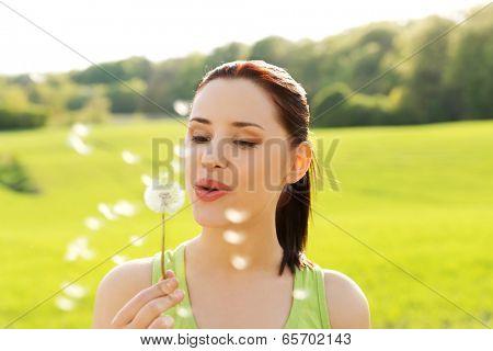 Woman blowing on a dandelion.