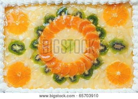 Fruity cake decorated with fruit mosaic on top of orange and kiwi. poster