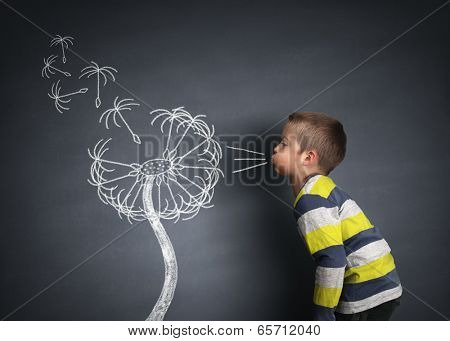 Child blowing dandelion seeds on a blackboard concept for wishing, hope and aspirations