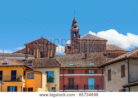 Bell tower of catholic church among typical colorful italian houses in town of La Morra in Piedmont, Northern Italy.