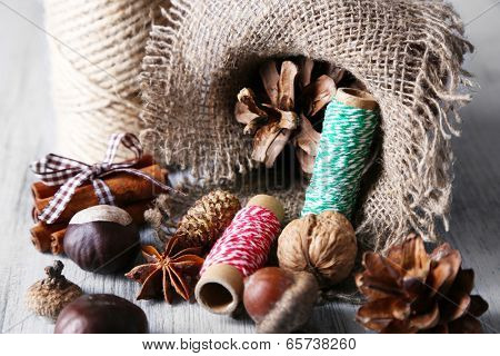 Composition with natural bump, thread, cinnamon sticks on wooden background poster