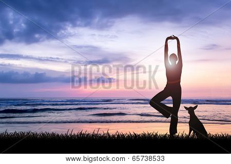 Young woman practicing yoga at sunset