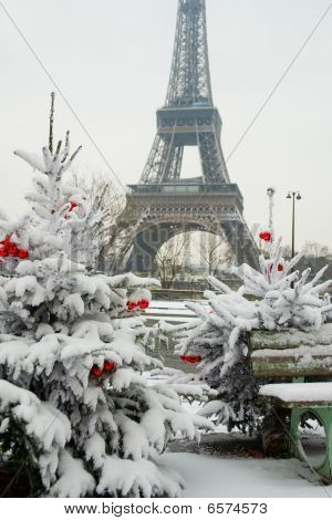 Rare Snowy Day In Paris. The Eiffel Tower And Decorated Christmas Trees