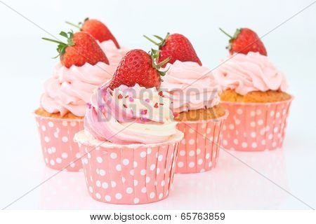 Delicious vanilla cupcake with strawberry frosting and fresh strawberry