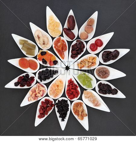 Dried fruit selection in white dishes over slate background.