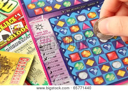 Coquitlam BC Canada - May 25, 2014 : Scratching lottery tickets. The British Columbia Lottery Corporation has provided government sanctioned lottery games in British Columbia since 1985.