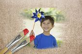 Composite image of little boy with pinwheel against weathered surface with paintbrushes poster
