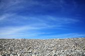 Coastline beach pebble stones and blue sky background with plenty of copy space poster