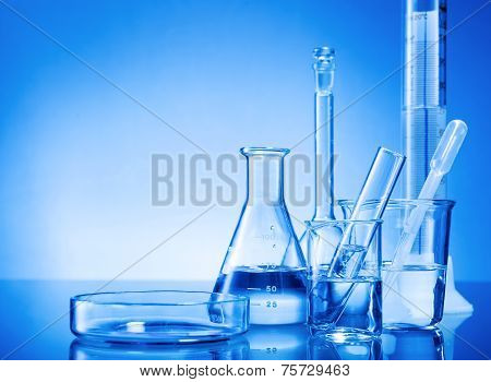 Laboratory equipment glass flasks pipettes on blue background