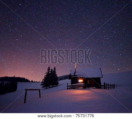 Wooden house with a light in the window. Night landscape in winter