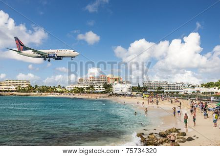 PHILIPSBURG, SINT MAARTEN - DECEMBER 30, 2013: A jet approaches Princess Juliana Airport above onlookers on Maho Beach. The short runway gives beach goers close proximity views of the planes.