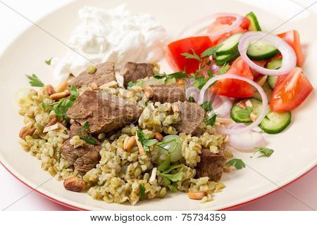 Beef, cooked with onion and spices and served on a bed of frikeh,with a salad and yoghurt and garnished with nuts.