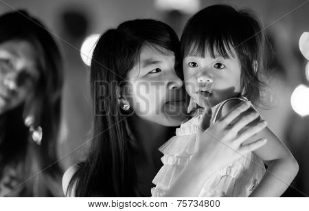 Chiang Mai, NOVEMBER 16, 2013: A young mother is holding her daughter during the Yee Peng lantern buddhist festival in Chiang Mai, Thailand