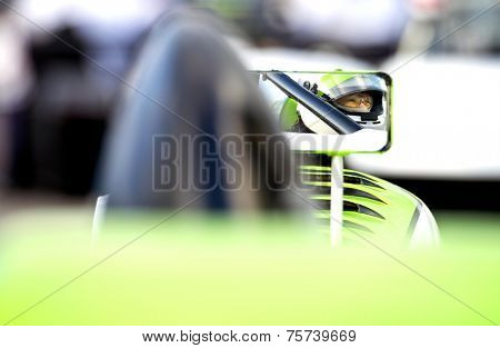 The nervous, tencely concentrated look in the eyes of a race car driver in his car on the starting grid of a race track, reflected in the side mirror of his vehicle. poster