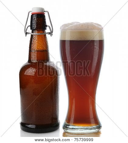 Closeup of a glass of dark beer with a frothy head next to a swing top brown beer bottle. Straight on shot on a white background with reflection. Both items are cover with water drops.
