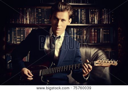 Handsome young man playing rock-n-roll music on his electric guitar. Retro, vintage style.