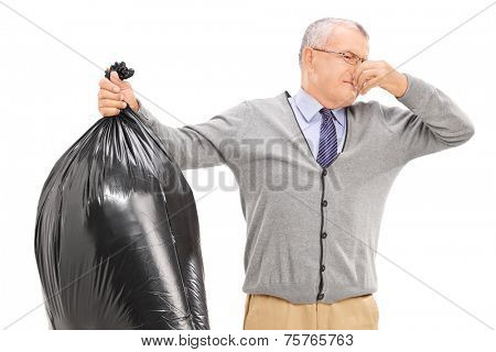 Senior holding a stinky garbage bag isolated on white background