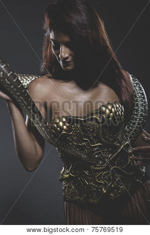 Sensual tattooed woman with big snake and iron corset poster