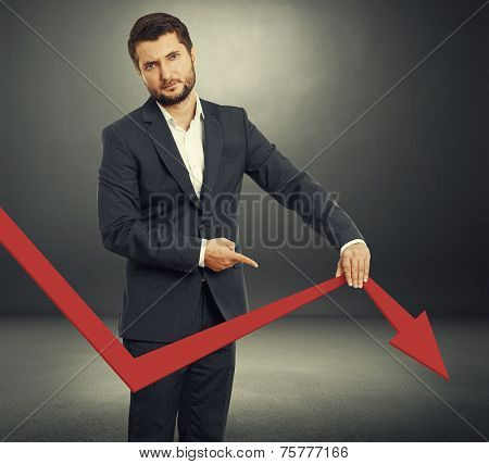 sad broker holding and pointing at falling down graph. photo over dark background