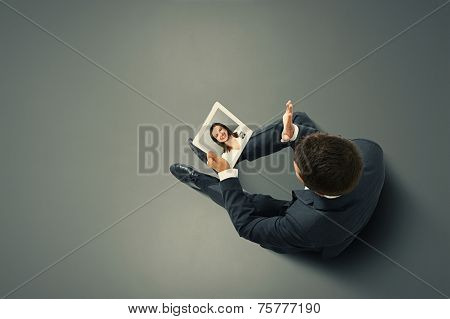 businessman sitting on the floor, holding tablet pc and waving his hand to young smiley woman. photo in the dark room