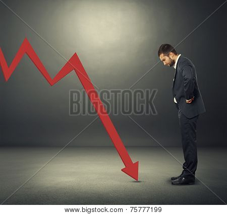 displeased businessman looking at red downturn graph. photo over dark background