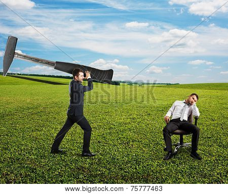 displeased boss holding big hammer and screaming at lazy worker. photo at outdoor