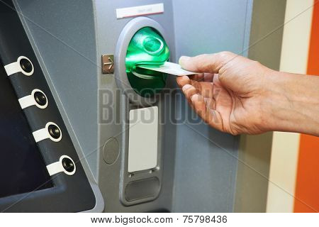 Cash withdrawal. hand inserting plastic card into the ATM