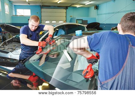 Automobile glazier adding glue on windscreen or windshield of a car in auto service station garage before installation poster