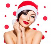 Christmas Woman. Beauty Model Girl in Santa Hat isolated on White Background. Holiday make up. Funny Smiling Surprised Woman Portrait. Red Lips and Manicure. Beautiful Holiday Makeup poster
