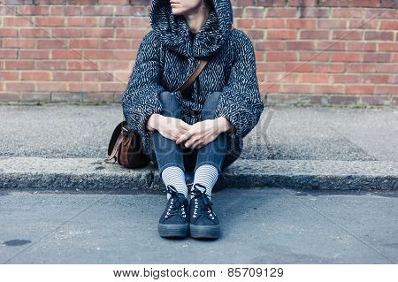 Young Woman Sitting Ion The Street