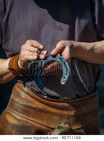 Farrier Showing two Horsehoes