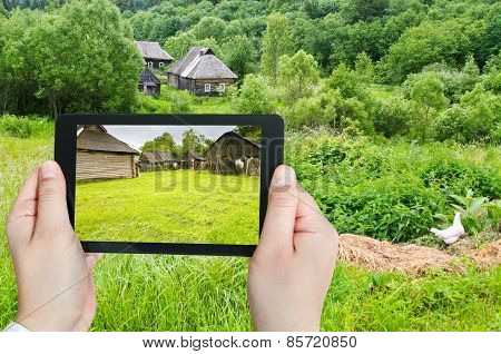 travel concept - tourist takes picture of backyard in peasant household in russian village on smartphone Smolensk region poster