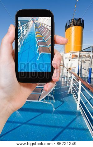 travel concept - tourist takes picture of sunbath chairs on upper deck of cruise liner on smartphone poster