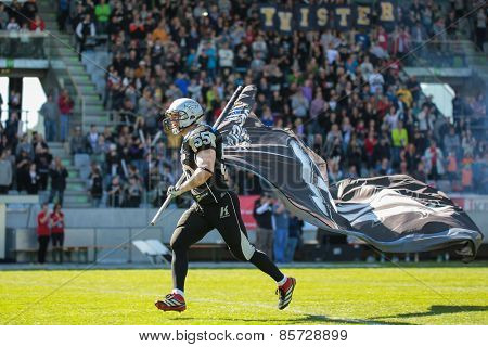 INNSBRUCK, AUSTRIA - MARCH 29, 2014: LB Christoph Schilcher (#55 Raiders) leads his team on the field before an AFL football game.