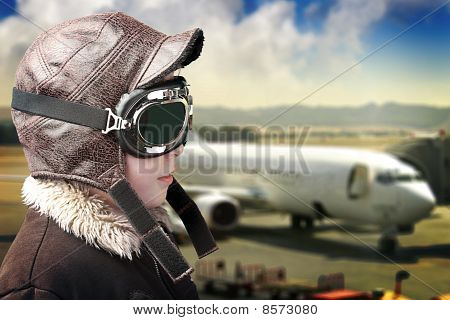 Boy Playing With Pilot´s Hat And Airport Background