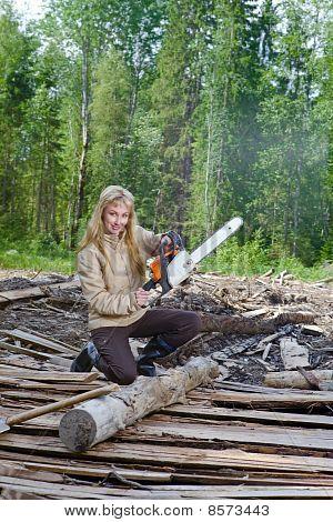 Sierras de la joven en madera de un árbol una motosierra