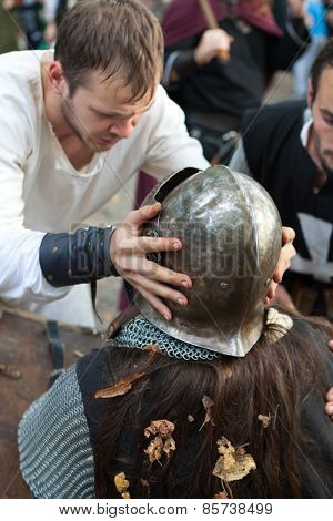 ZAGREB, CROATIA - OCTOBER 07, 2012: Squire helping the knight with his helmet at