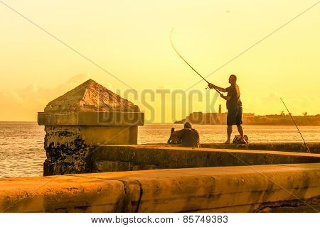HAVANA,CUBA : MARCH 12, 2015 : Man fishing at the Malecon seawall during a sunset in Havana