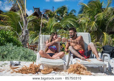 Cute Couple Drinking Coconut At Tulum Caribbean Beach. Riviera Maya Traveling Through Mexico.