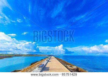 Blue sky and the breakwater with benches