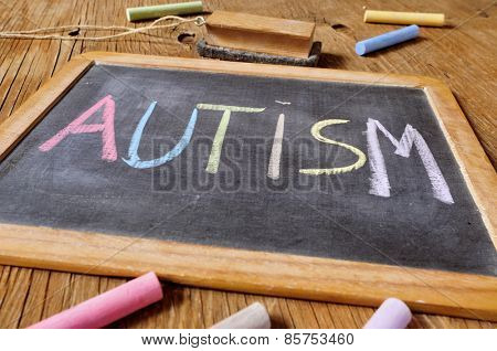 the word autism written with chalk of different colors in a chalkboard placed on a rustic wooden desk or table